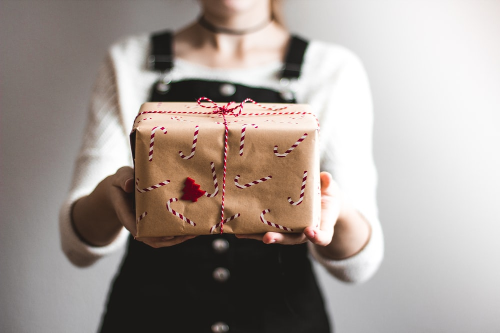tilt-shift lens photography of woman holding candy cane-print gift box in a well-lit room