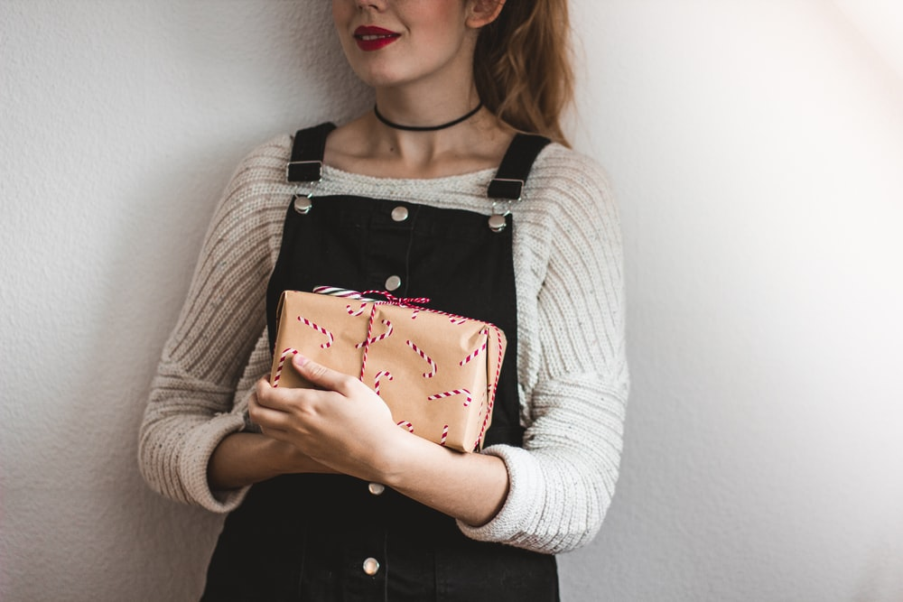 woman carrying brown leather bag while standing near white painted wall