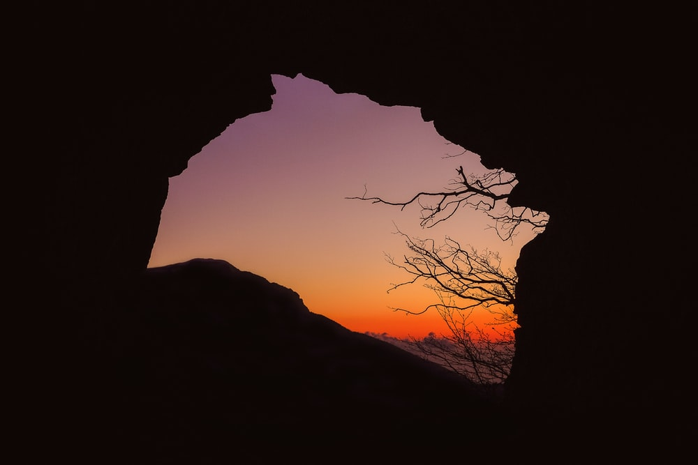 silhouette of cave during sunset