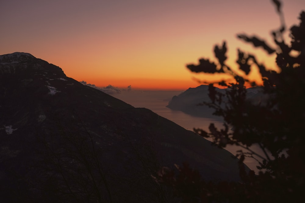 high-angle silhouette photography of mountain ranges with body of water in between during golden hour