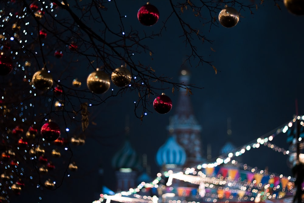 red and brown Christmas baubles hanging on trees near lighted buildings at night