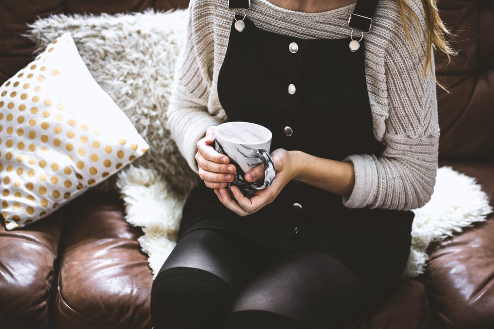 woman sitting on the sofa holding white and black ceramic mug