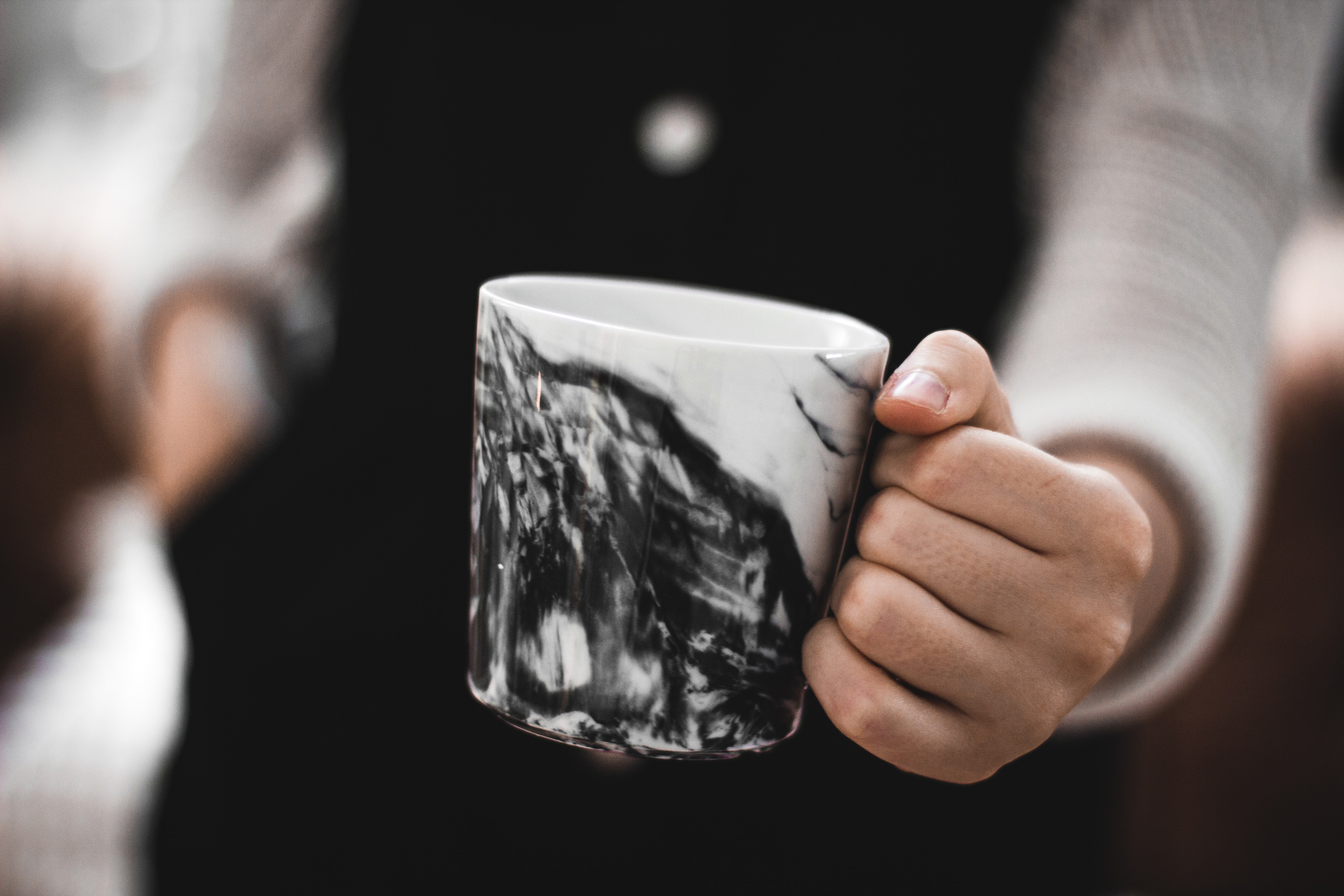 person holding a white and black ceramic mug