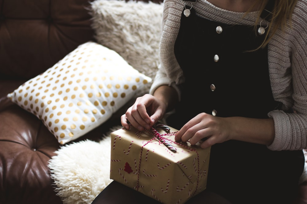 woman in grey sweater and blue denim dungarees sitting on brown and white sofa opening a yellow gift box closeup photography