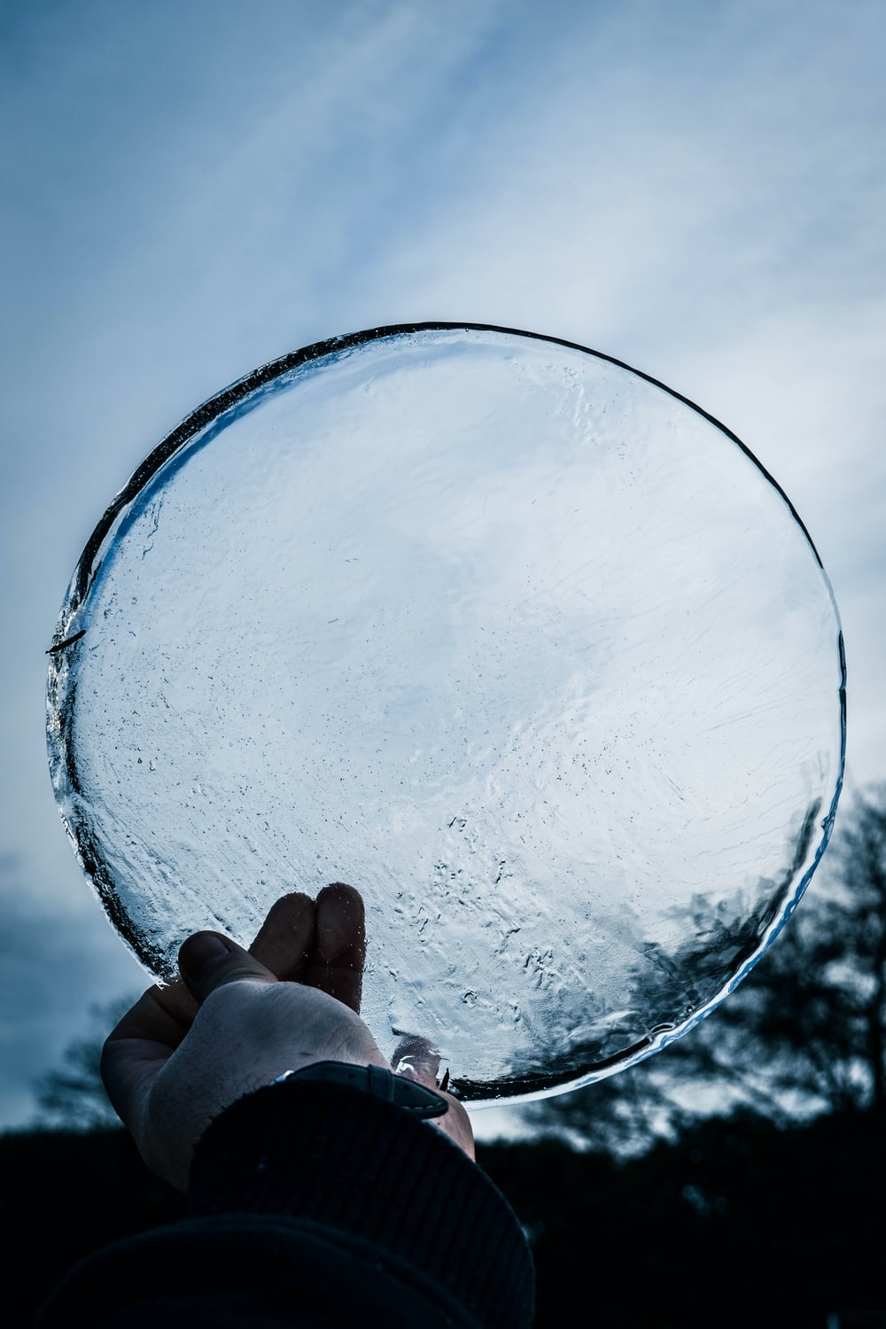 person holding round clear ice glass