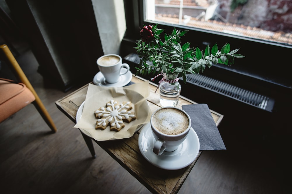 two cups of coffees on brown wooden coffee table besie glass window