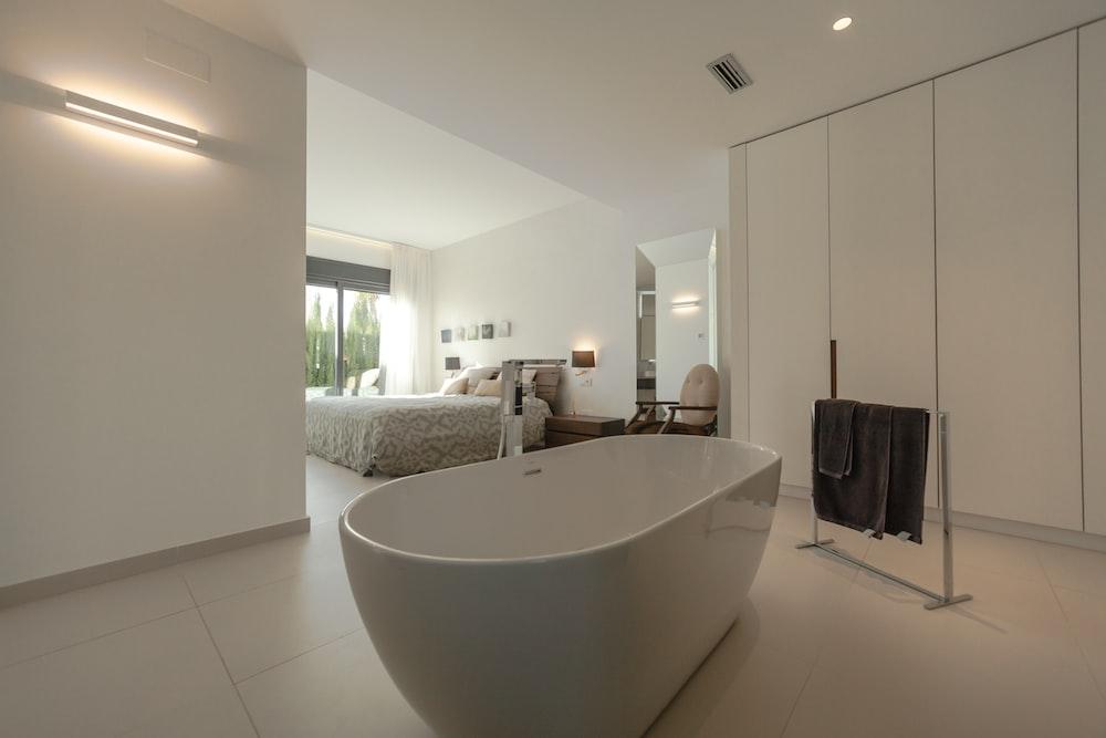 white ceramic bathtub near black textile