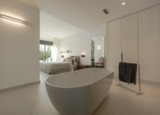 white ceramic bathtub near black textile