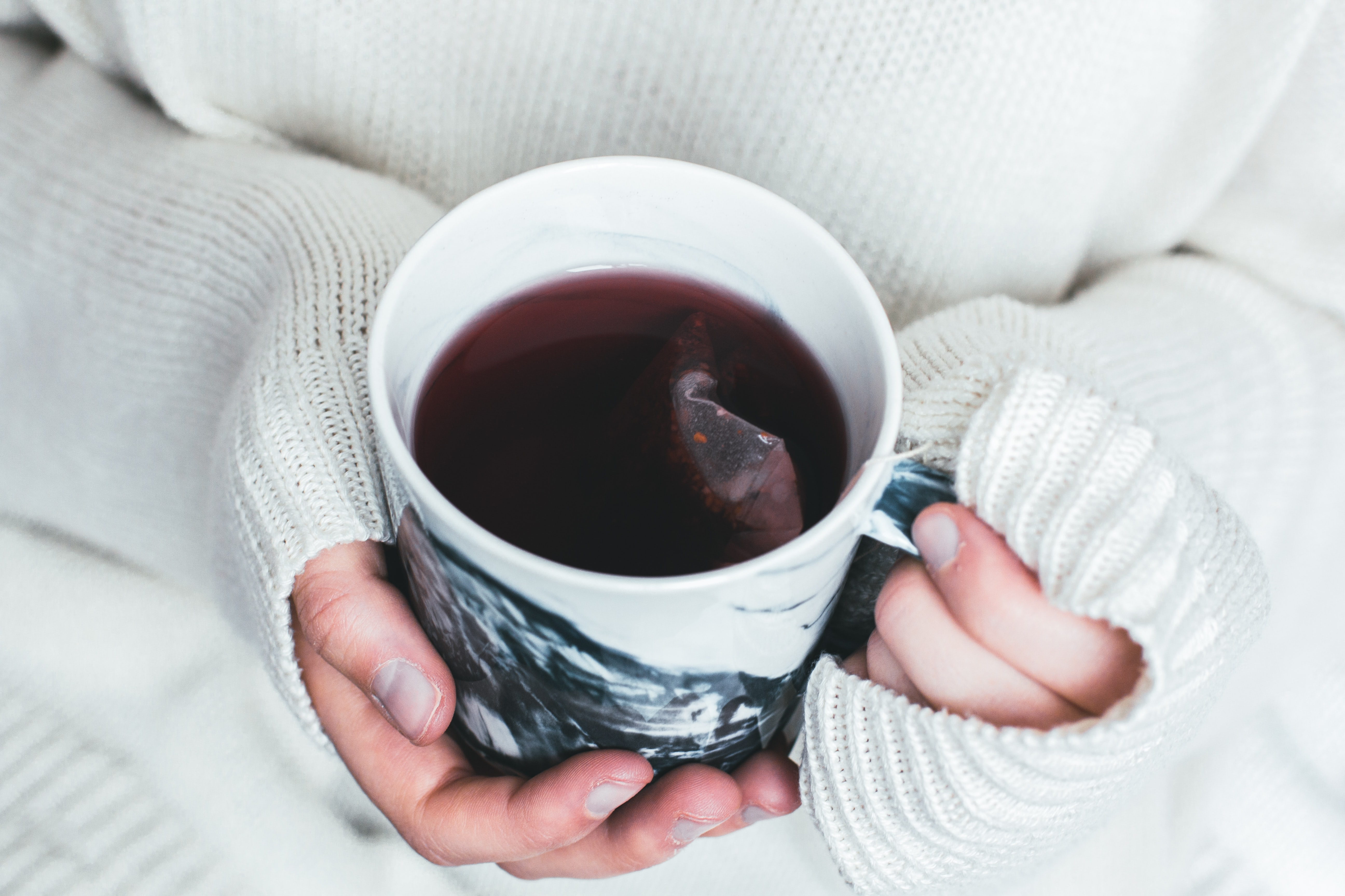 person holding white and black cup with teabag inside