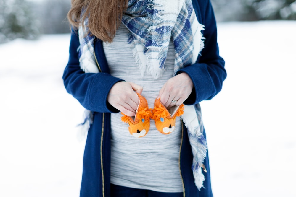 woman holding baby's orange animal shoes
