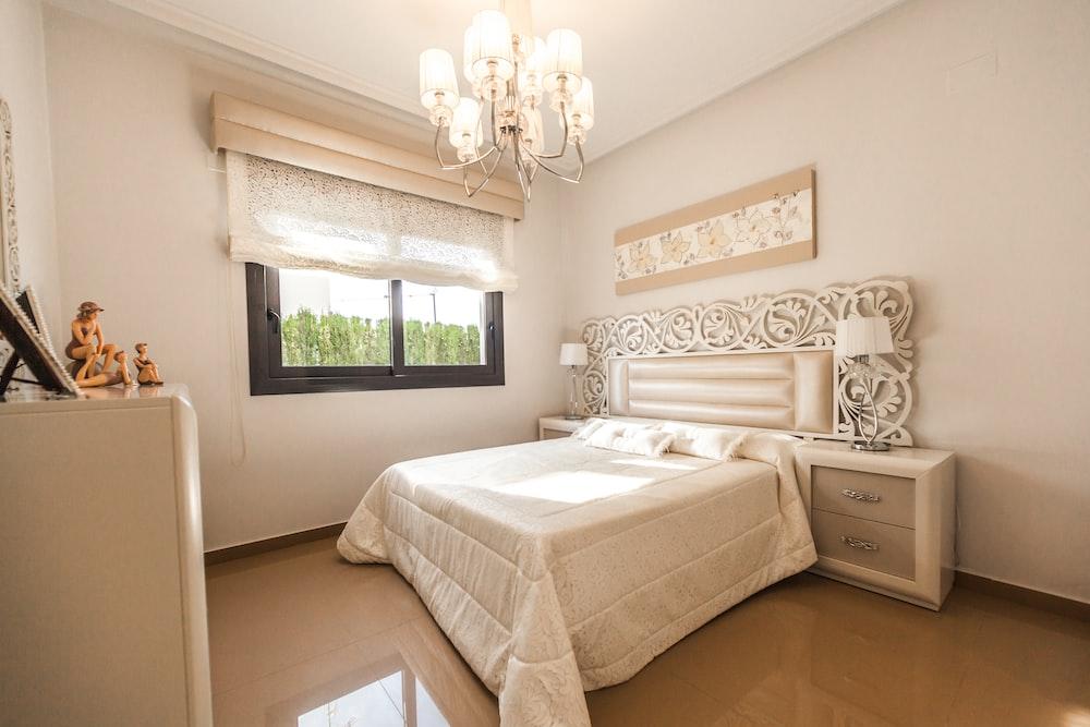 white bed comforter near glass window