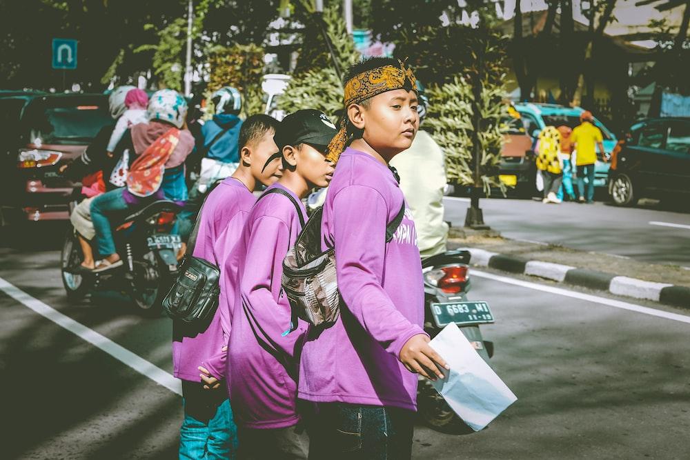 three boys in purple shirts crossing pedestrian lane