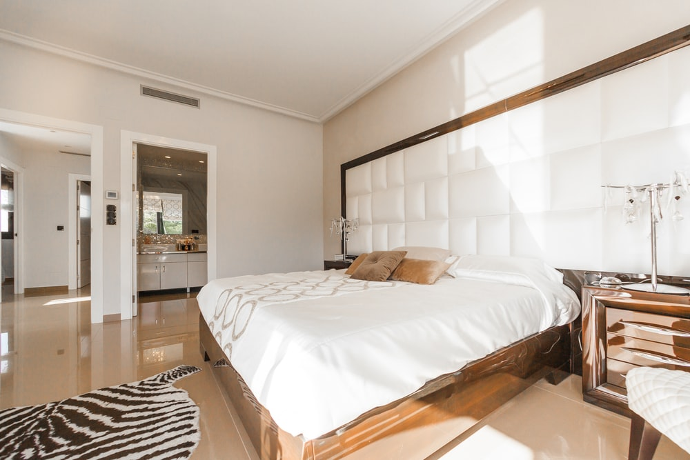 brown wooden bed frame with white cover beside brown wooden nightstand