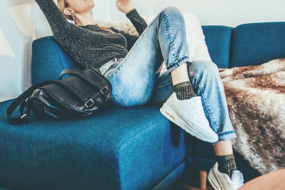 woman sitting on sofa beside bag