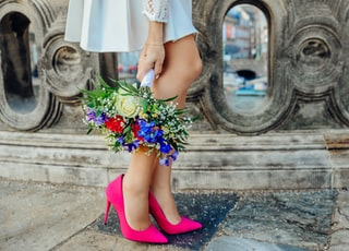 woman holding white, blue, and red petaled flower bouquet beside gray concrete fence