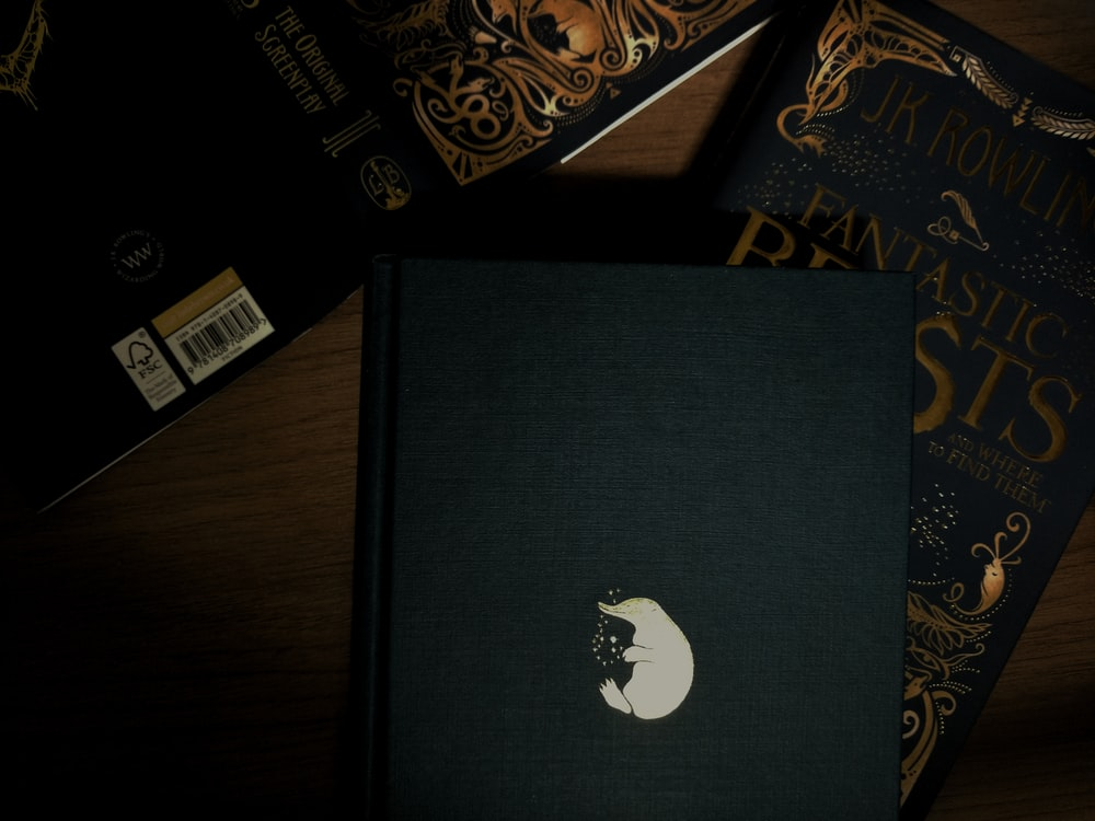 black Sony PS4 Slim near Fantastic Beasts by J.K. Rowling book on table