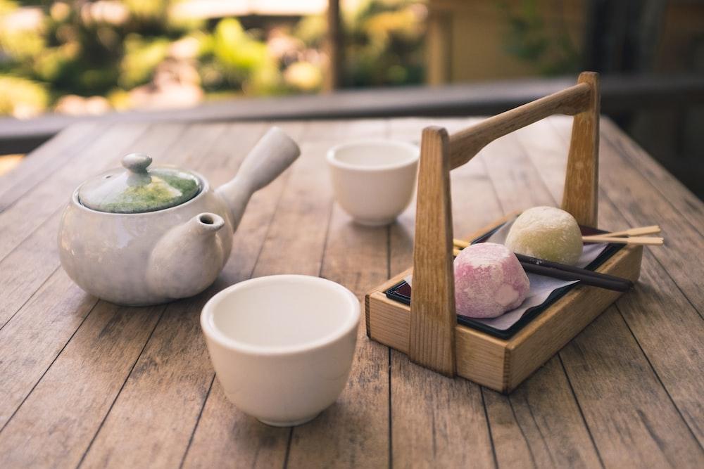 white ceramic mug near tea pot on table