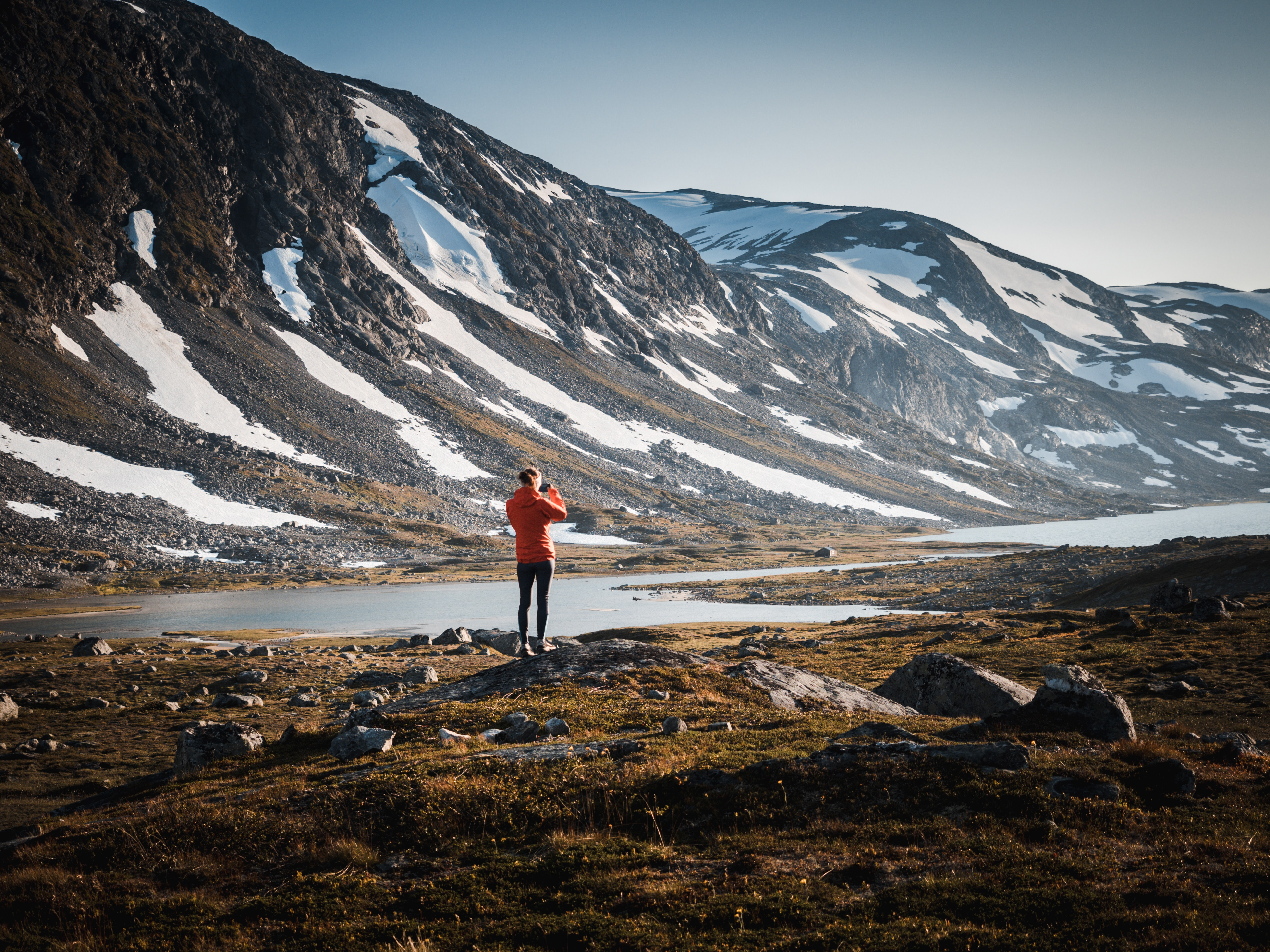 person standing on rock near body of water and mountain