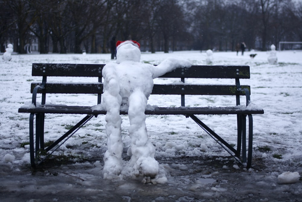 snowman on black wooden bench during daytime