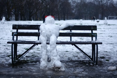 snowman on black wooden bench during daytime snowman zoom background