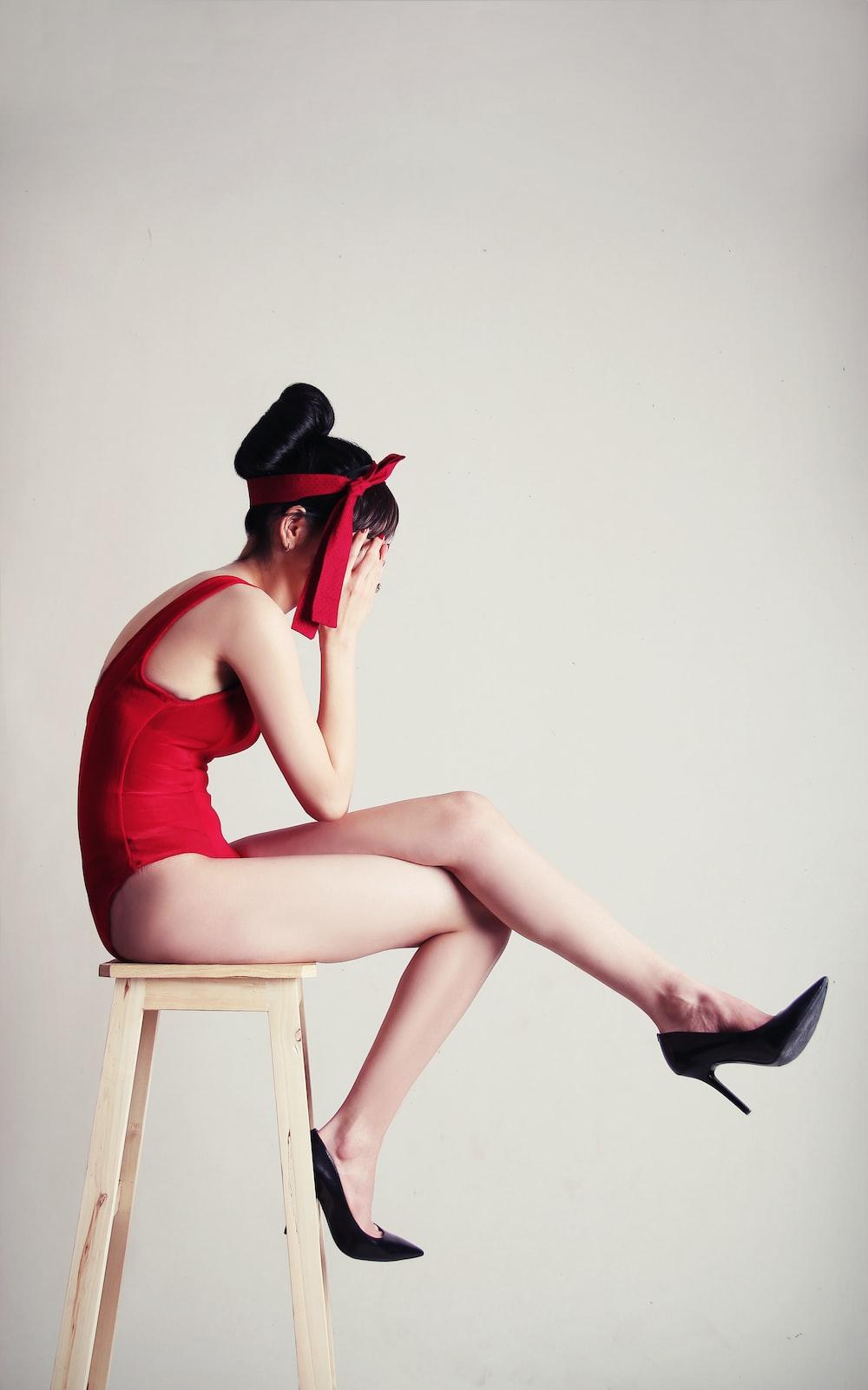 upset woman sitting on stool with white background
