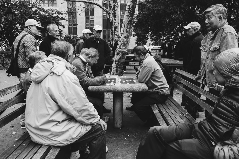 greyscale photo of people on park watching two people playing board game