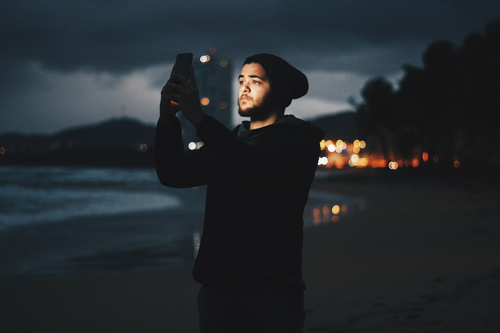 man using mobile phone on beach during dusk