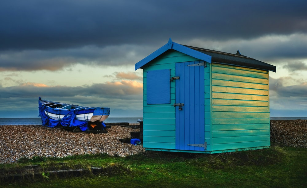 teal and blue wooden shed near boat