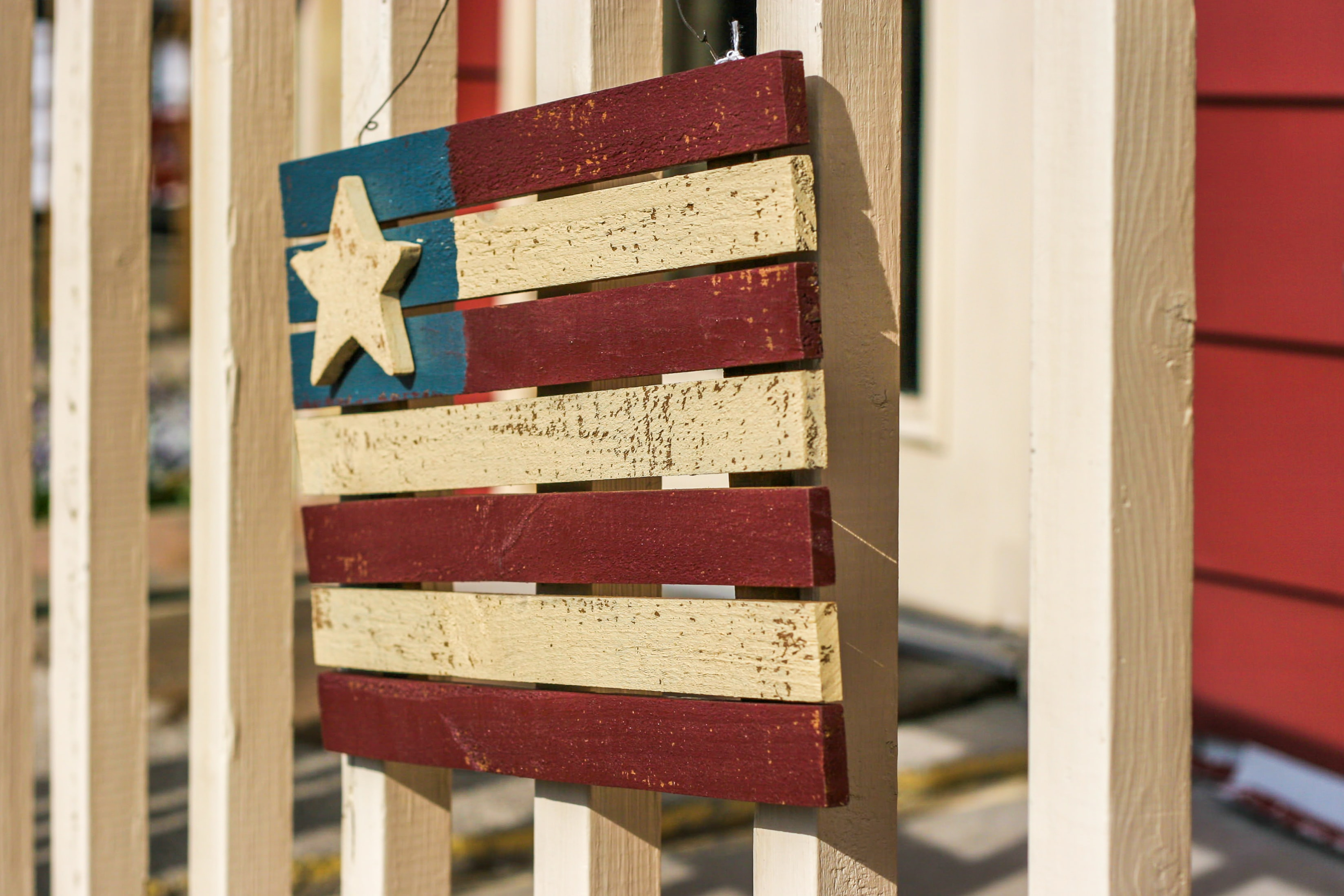 wooden USA flag hanging decor on white fence