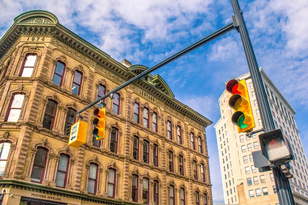 architectural photography of traffic lights near beige painted establishment