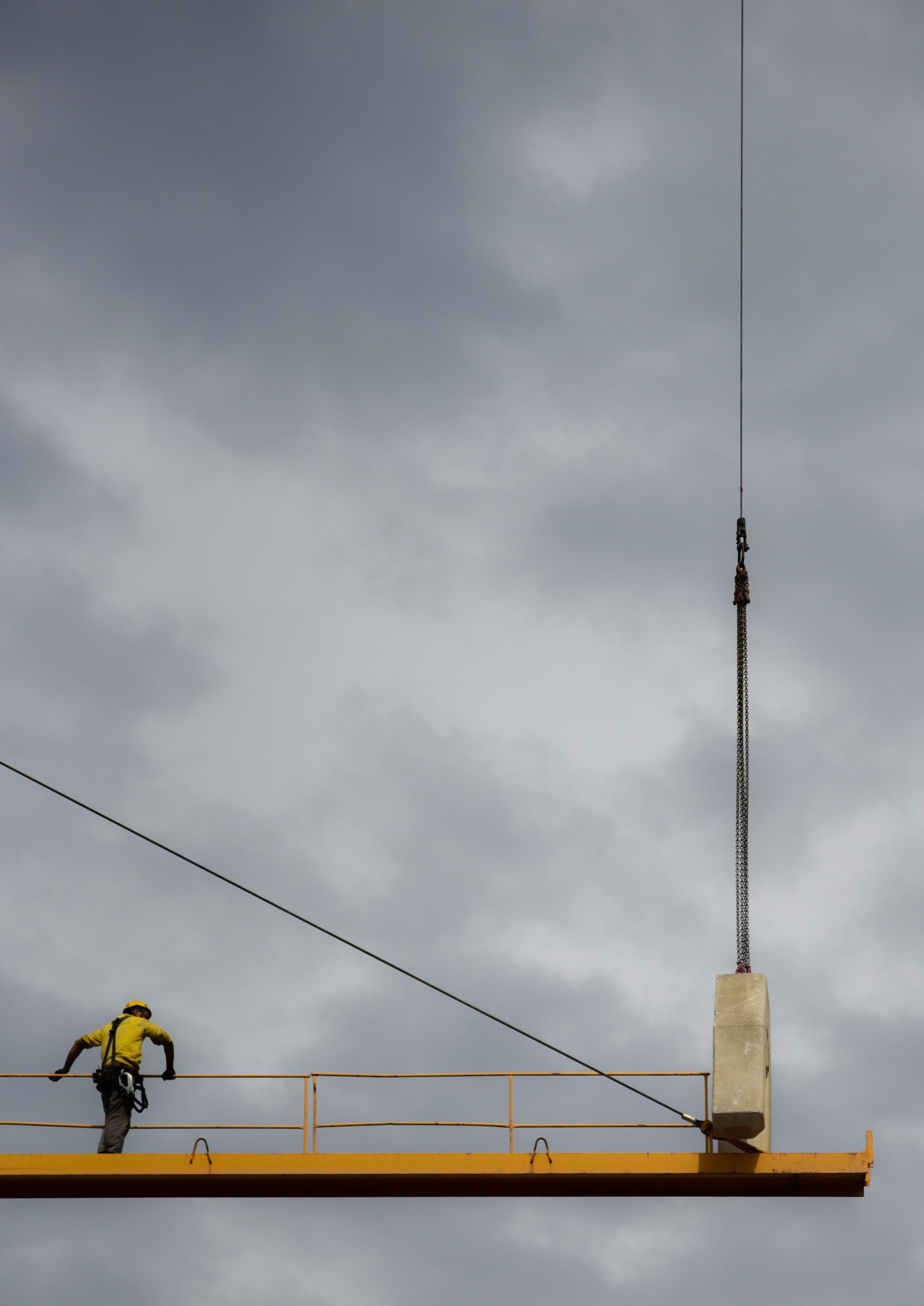 man wearing black harness strap holding yellow metal platform railing under blue cloudy skies at daytime