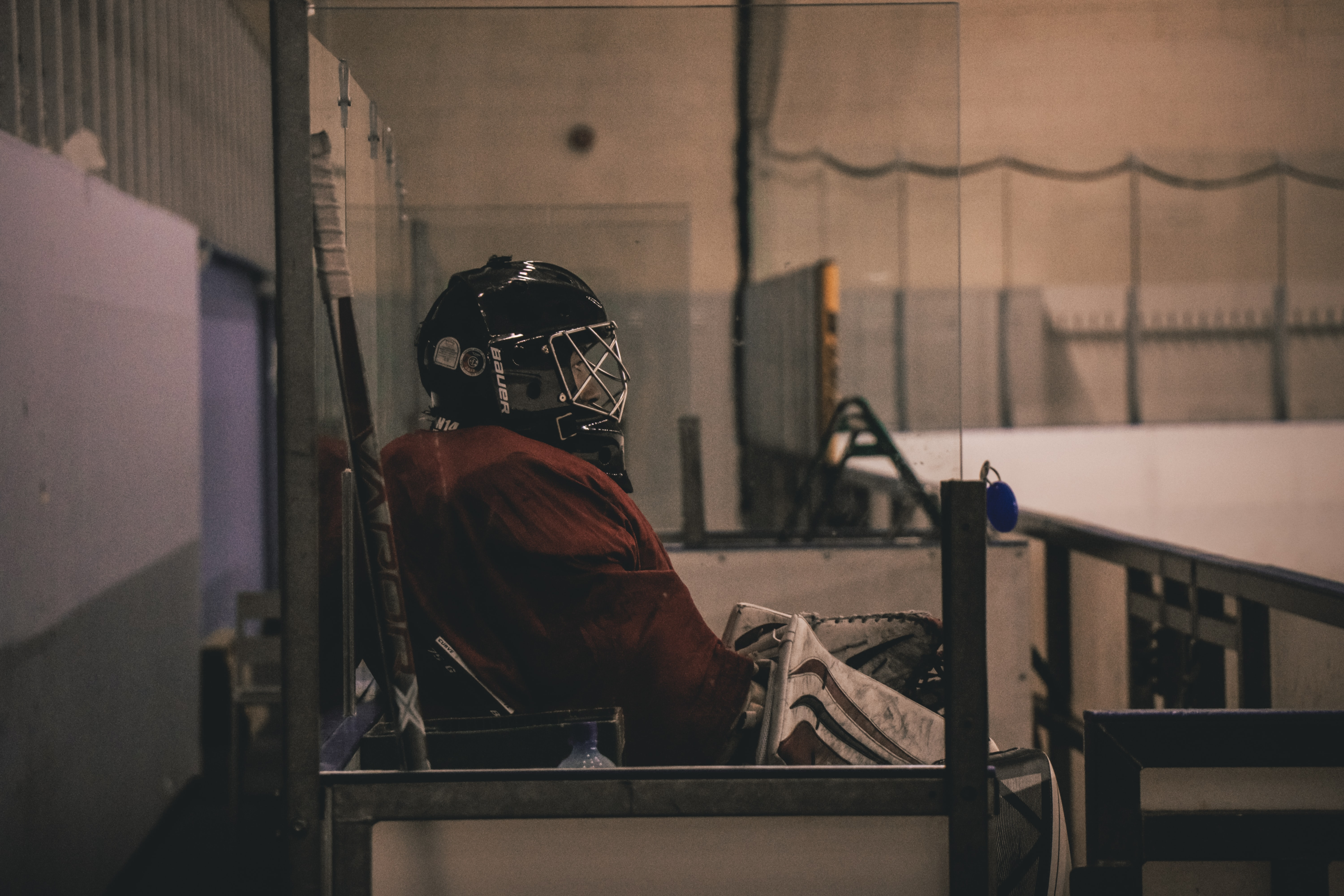 person sitting on bench wearing ice hockey jersey