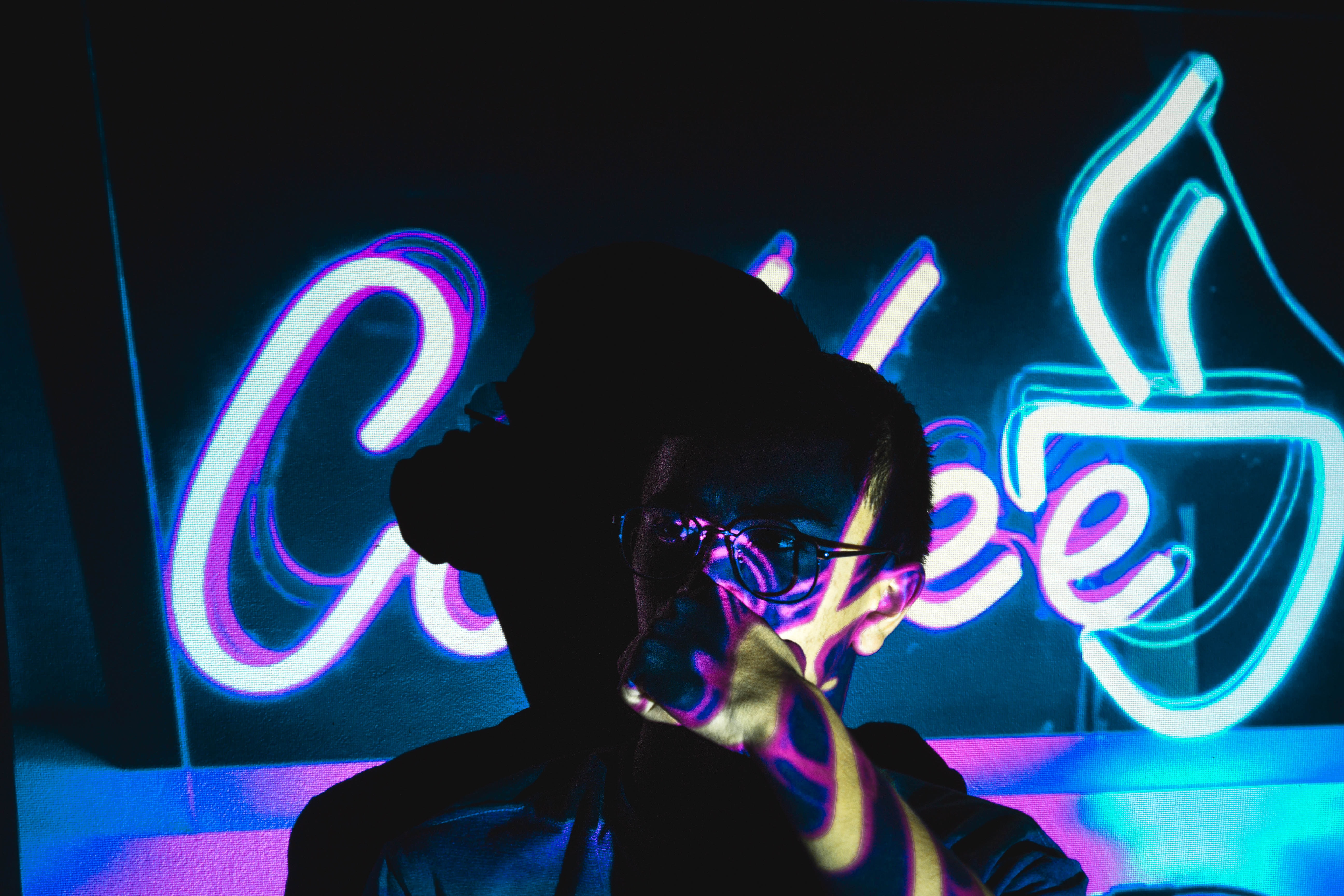 person wearing eyeglasses with shadow near neon light signage
