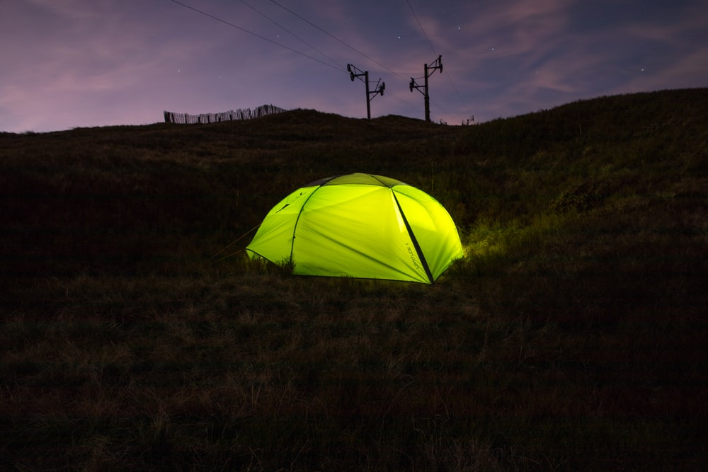 lightened green dome tent surrounded by green grass during daytime