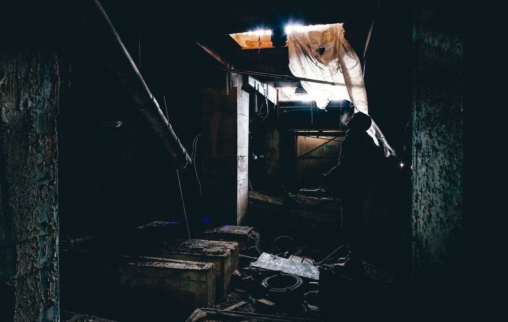 low-light photography of person inside messy room
