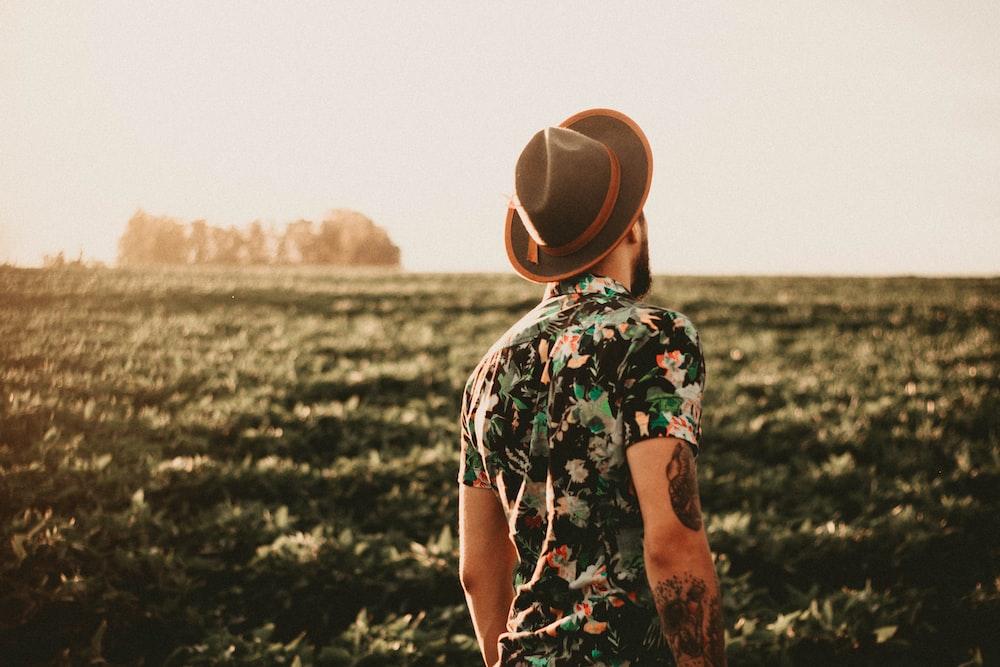 man wearing brown fedora hat standing near trees