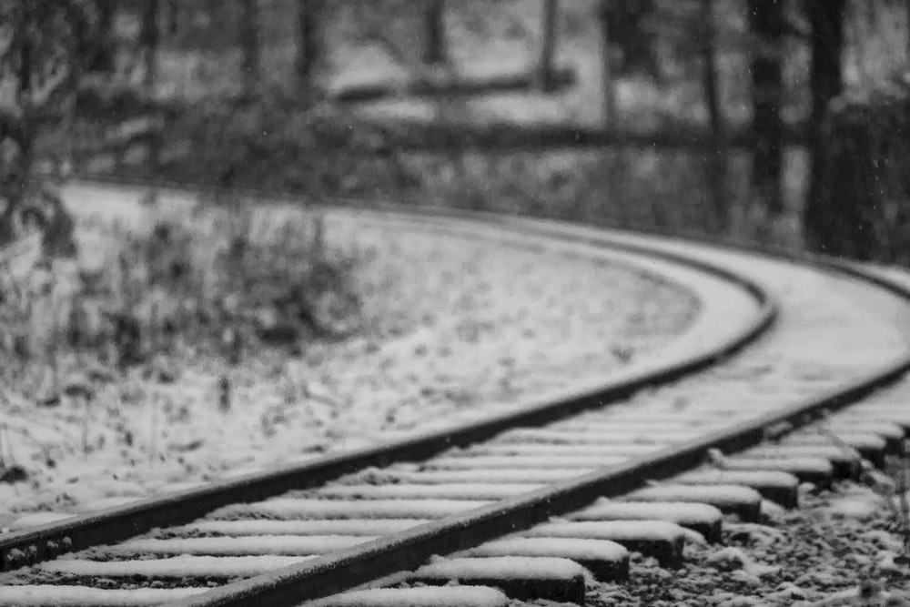 selective focus photography of black metal railroad covered with snow