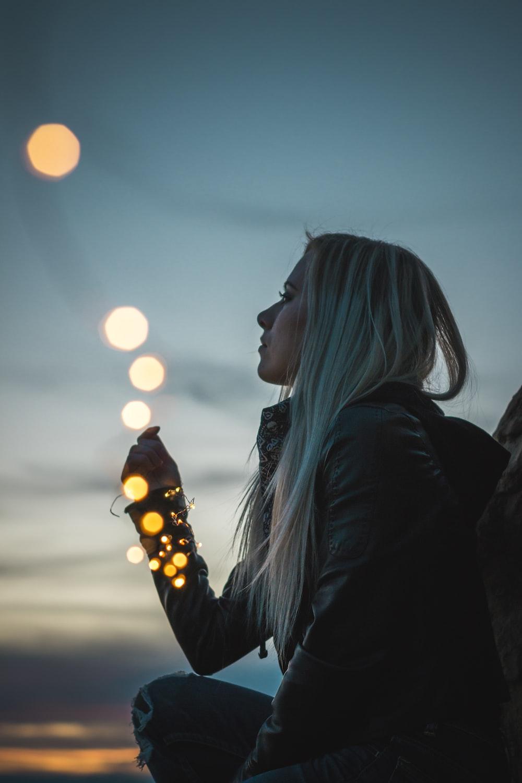 woman sitting holding string lights