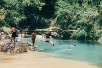 man diving at water with people at river daytime