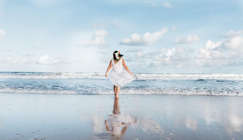 woman in white dress walking on shore at daytime