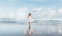 woman in white dress walking on shore at daytime
