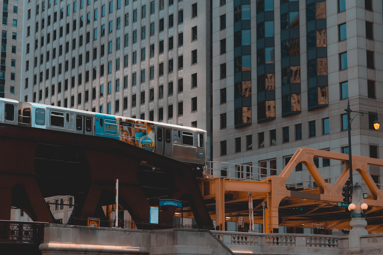 gray train in railway near high-rise building
