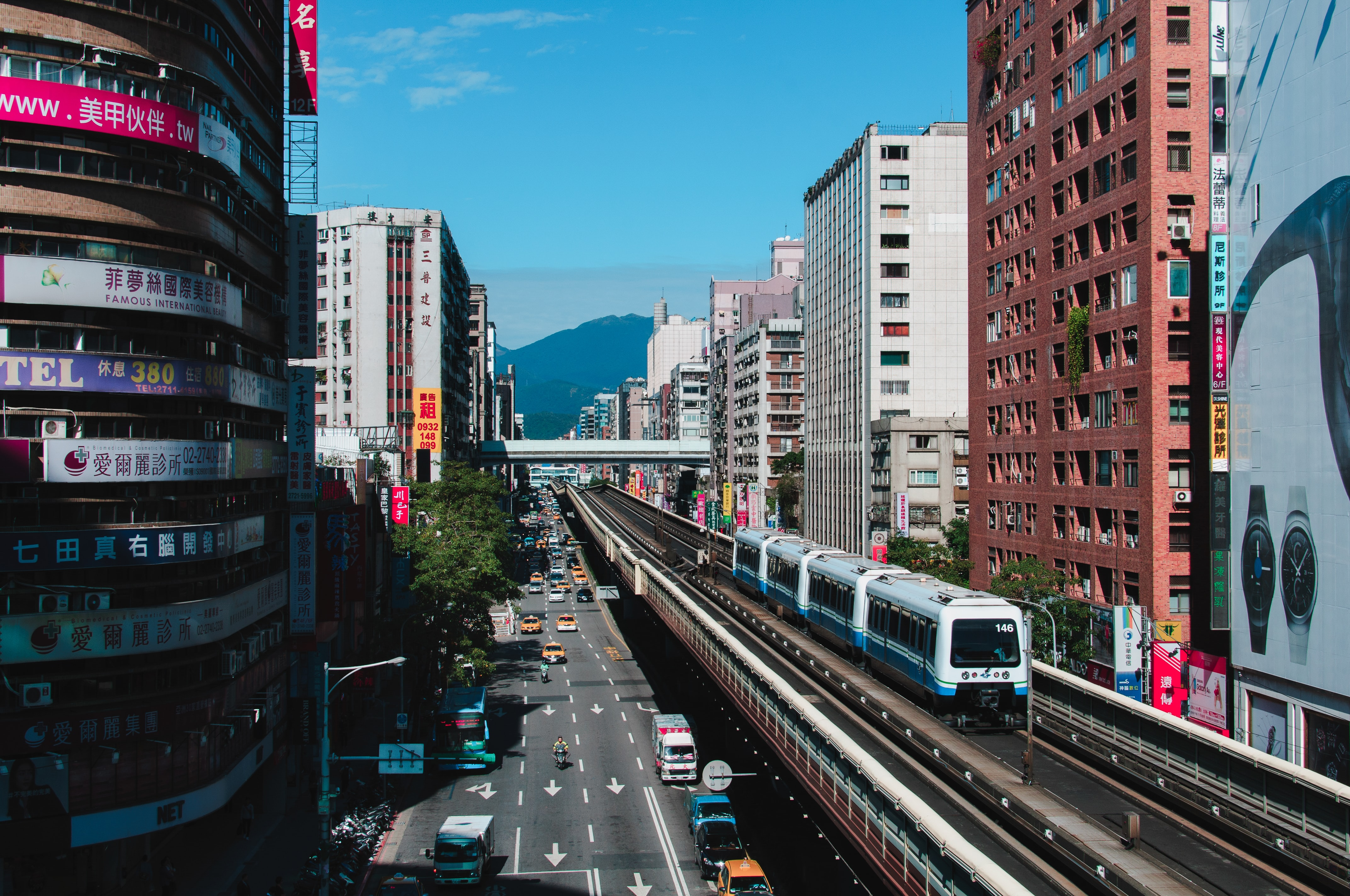 white and blue train near high-rise buildings during daytime
