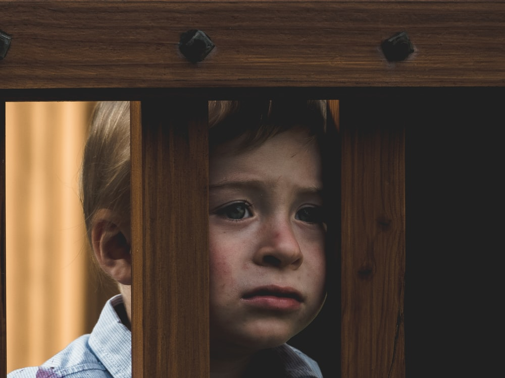 boy leaning on brown wooden railings