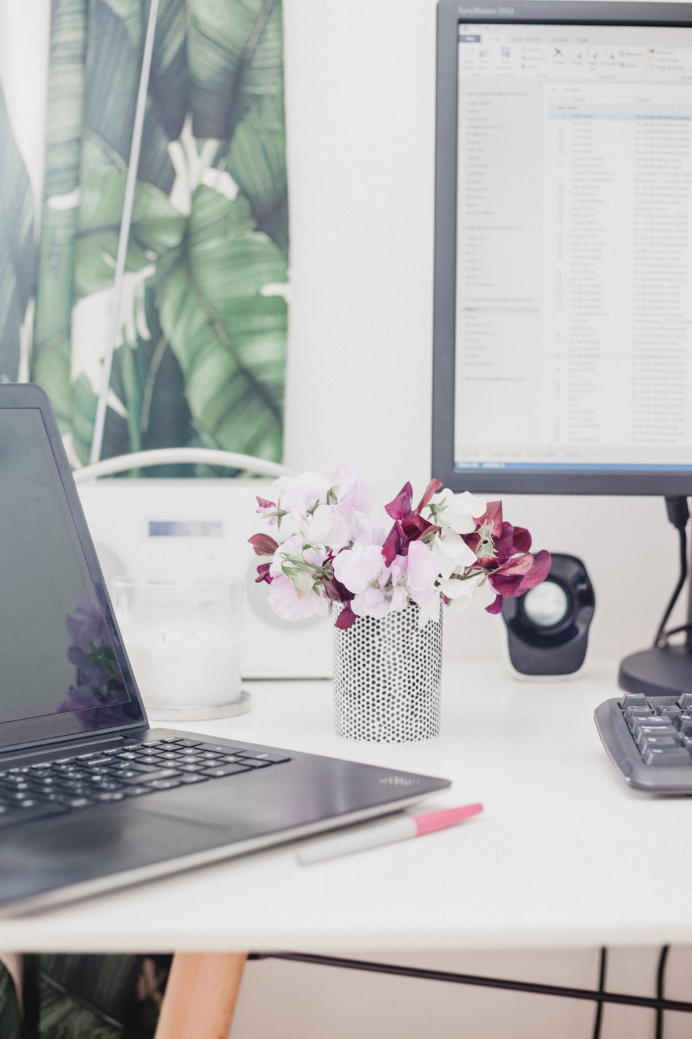 pink and red petaled flower on vase beside computers