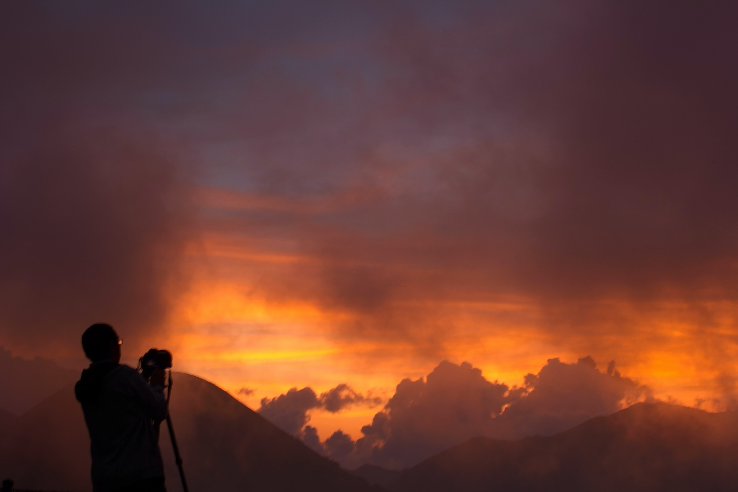 silhouette of person holding camera facing orange and yellow sky
