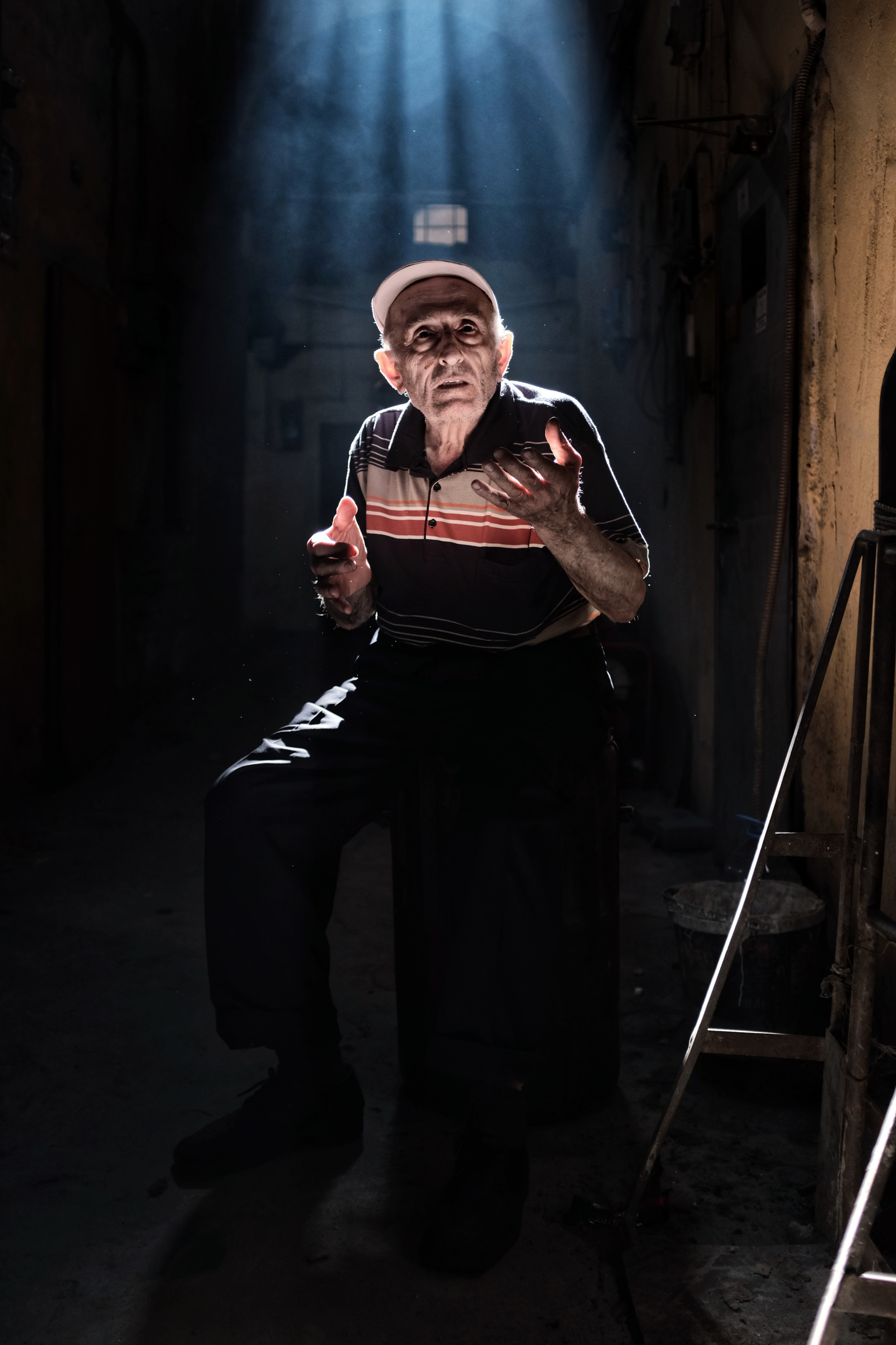 man wearing black and beige striped polo shirt and black pants sitting on stool with lights