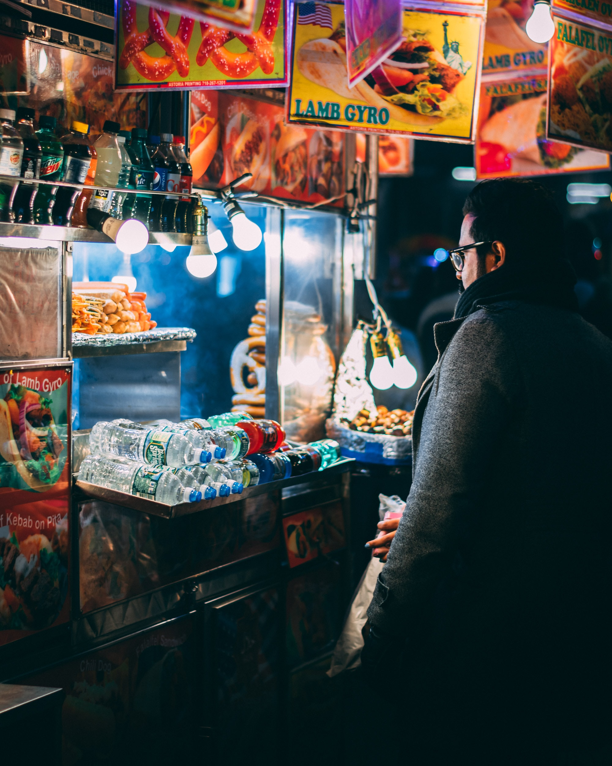 man with coat standing in front of food cart during nighttime