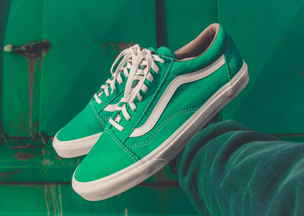 person holding pair of green Vans shoes