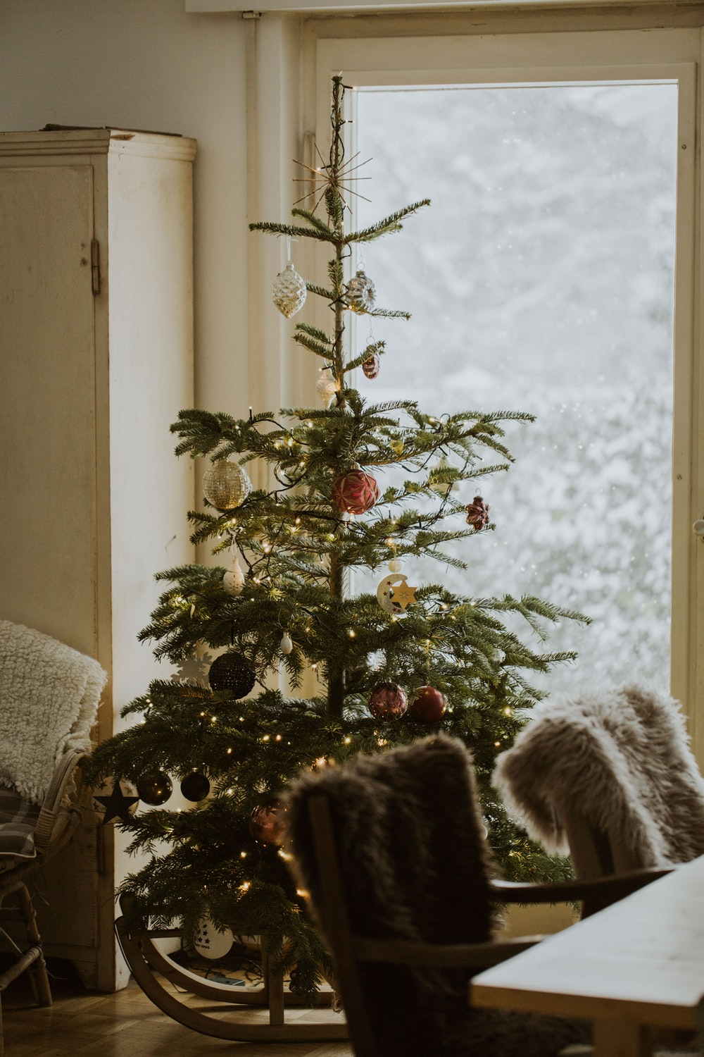 green Christmas tree with assorted-color baubles inside room